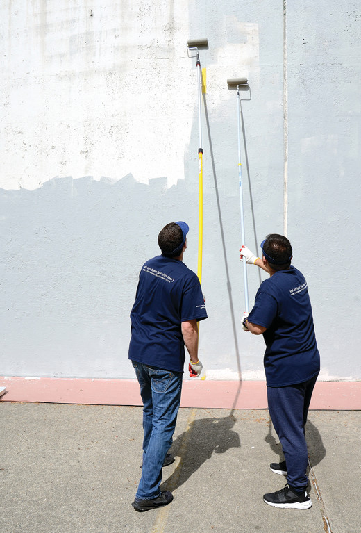Volunteers whitewash the handball wall during the first Archdiocesan Day of Service on April 29.