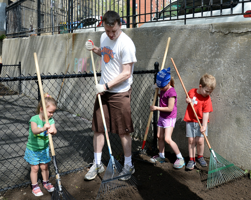 Nate Mathews and his children, Amelia, 2, Claire, 7, and Noah, 4, wield rakes during the first Archdiocesan Day of Service on April 29.