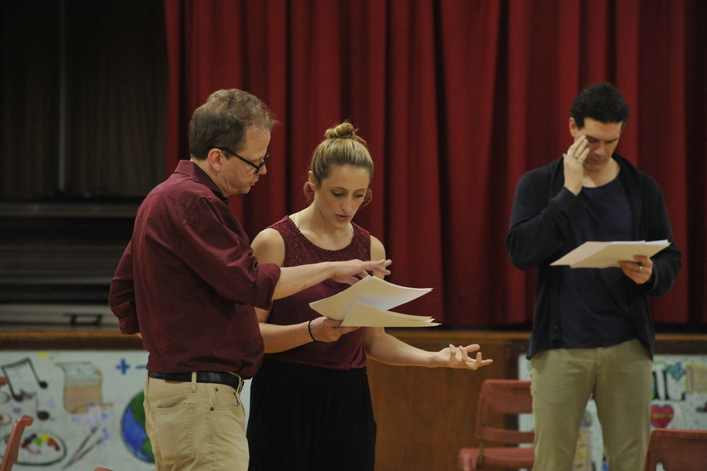 "REHEARSAL—Peter Dobbins, director of ""Death Comes for the War Poets,"" discusses a portion of the play with actress Sarah Naughton as actor Nicholas Carriere reads behind them during a rehearsal in May at Corpus Christi School in Manhattan."