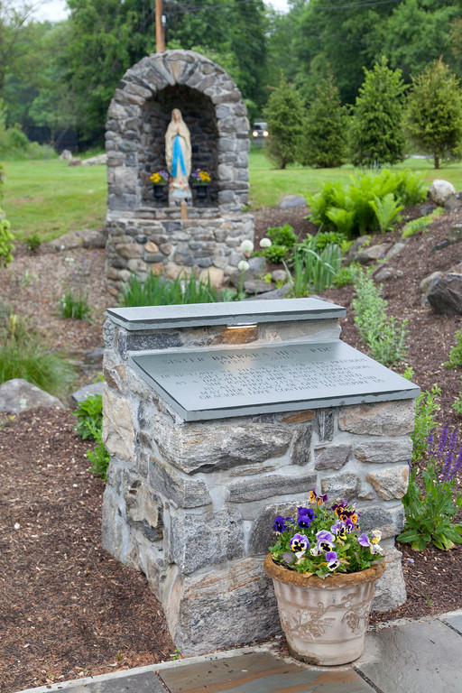 The grotto includes a garden, statue of the Blessed Mother and a dedication plaque.