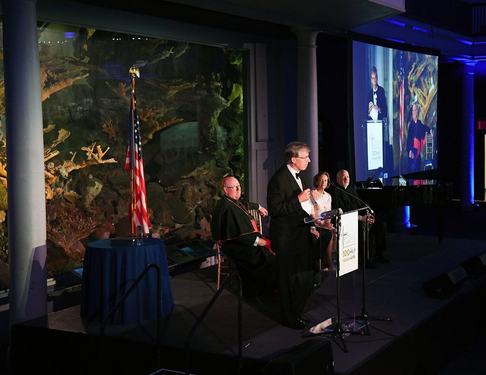 Robert H. Niehaus, Chairman and Founder, GCP Capital delivers his acceptance remarks. Behind him is Cardinal Dolan on the left.  On the right is Catherine R. Kinney, Chair, The Catholic Charities of the Archdiocese of New York Board of Trustees; and Msgr Sullivan.