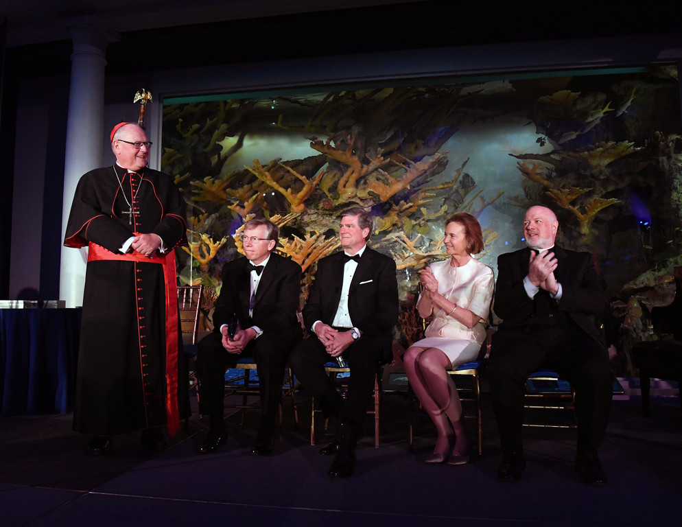 Left to right:  Cardinal Dolan, who had just concluded his remarks waits for the applause to subside; Robert H. Niehaus, Chairman and Founder, GCP Capital;  John G. Stratton, Executive Vice President and President of Customer and Product Operations, Verizon;  Catherine R. Kinney, Chair, The Catholic Charities of the Archdiocese of New York Board of Trustees; and Msgr Sullivan.