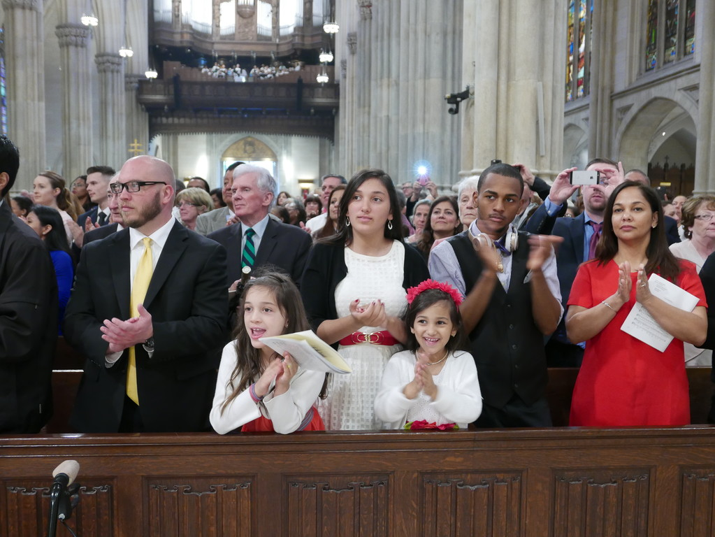 PROUD—Family members and friends of the new deacons eagerly display their joy and enthusiasm at the Mass of Ordination.