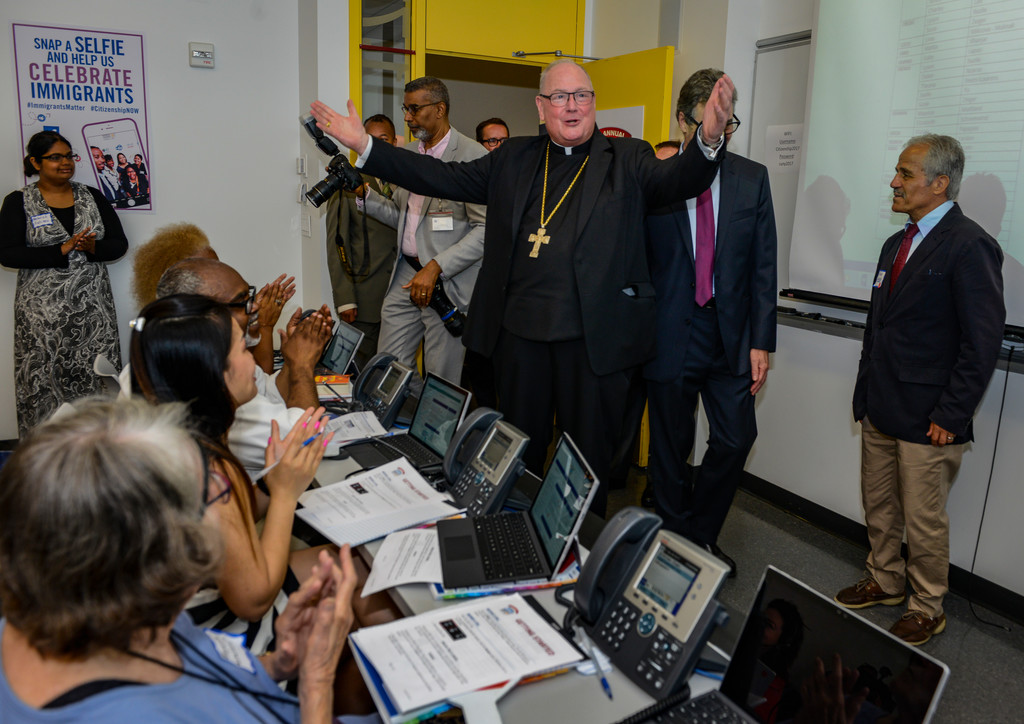 RALLYING THE TROOPS—Cardinal Dolan exhorts volunteers June 19 at the 15th annual CUNY/Daily News Citizenship Now! phone bank. Volunteers were providing free immigration advice to callers. Attorneys were also on hand to answer questions at the event, which is scheduled to run through June 23.
