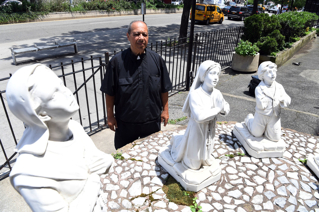 Father Mario Julian, O.F.M., pastor of St. Anthony of Padua parish in Manhattan, gazes at the parish's outdoor statues that depict the apparition of Our Lady of Fatima to three shepherd children in Fatima, Portugal.