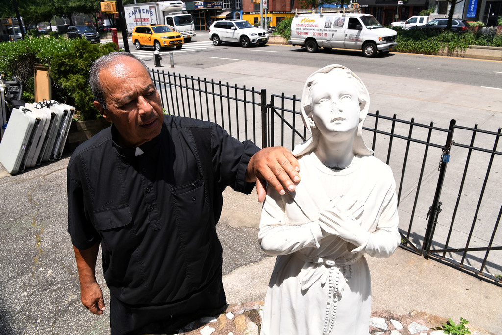Father Julian stands next to the statue of Lucia dos Santos, which is now missing a nose.