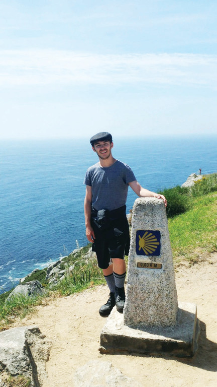 Christopher Nadramia, a parishioner of St. Columbanus in Cortlandt Manor, stands at the end of the Camino de Santiago journey where a marker indicates that zero kilometers remain.