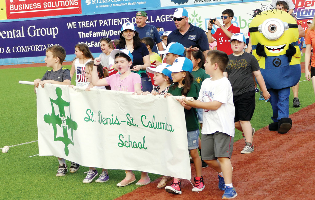 Students of St. Denis-St. Columba School in Hopewell Junction join a pregame parade for participating Catholic schools before the Hudson Valley Renegades baseball game against the Staten Island Yankees at Dutchess Stadium in Fishkill June 22.