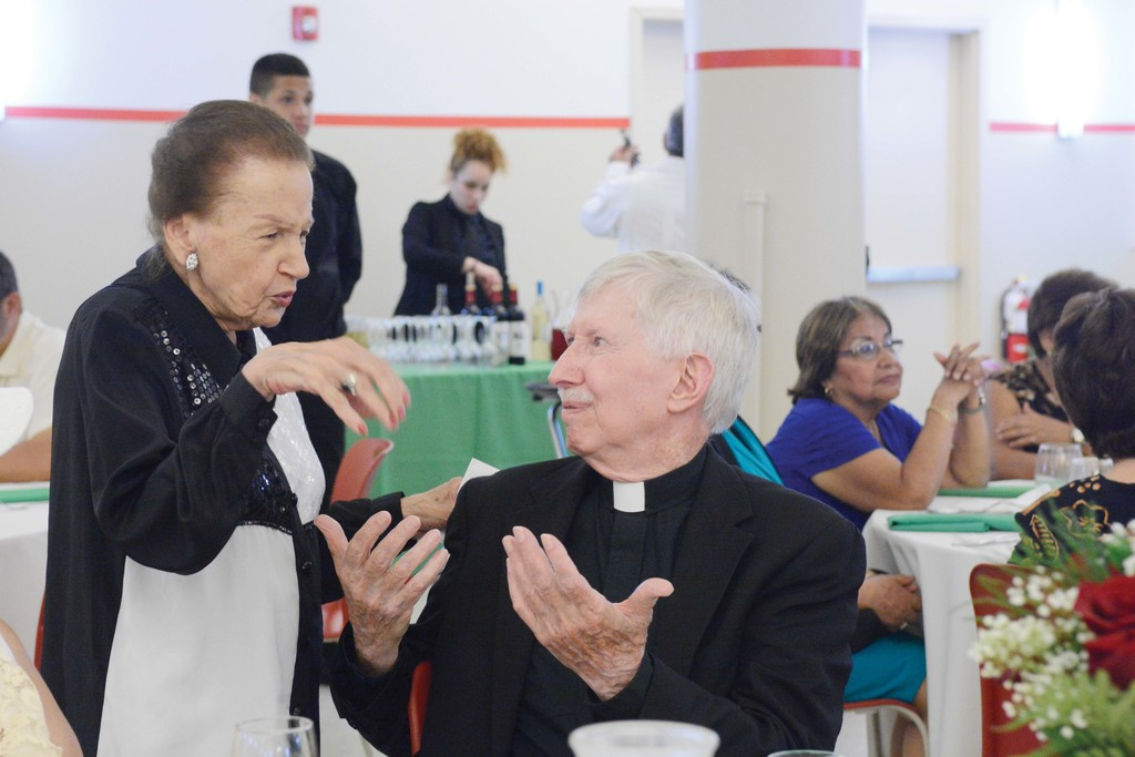 Angela Cabrera, president emeritus of the Comite Fiesta de San Juan Bautista, converses with Father Stern at the awards dinner.