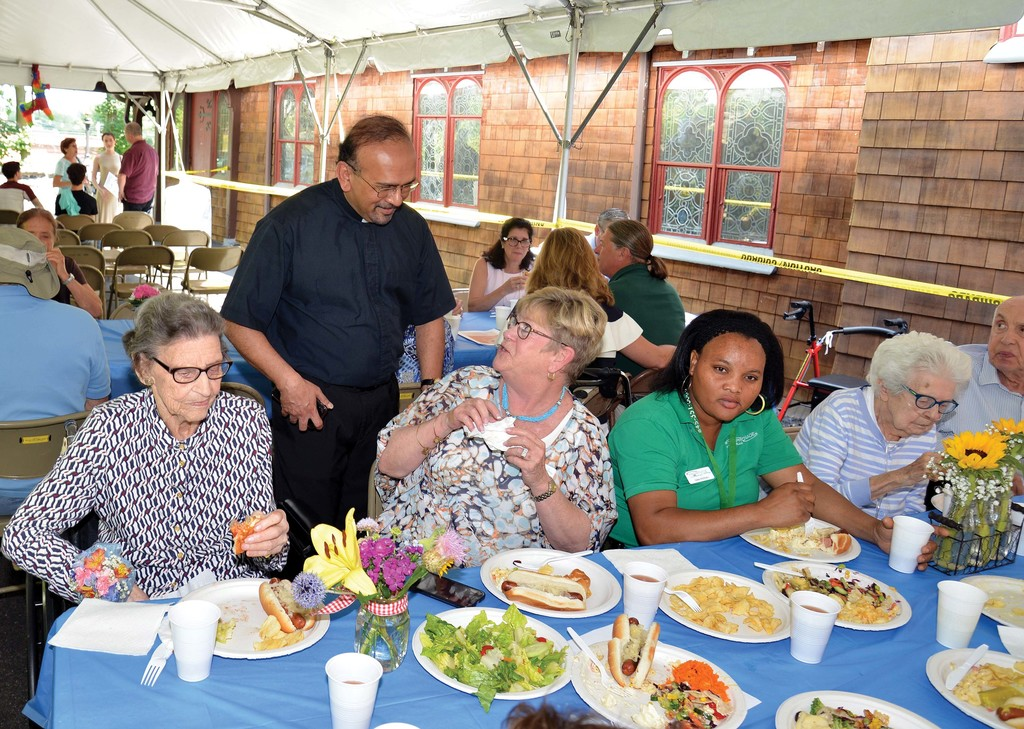 A reception and picnic followed on the church grounds, where Father Rodrigo is pictured chatting with parishioners and picnic-goers.