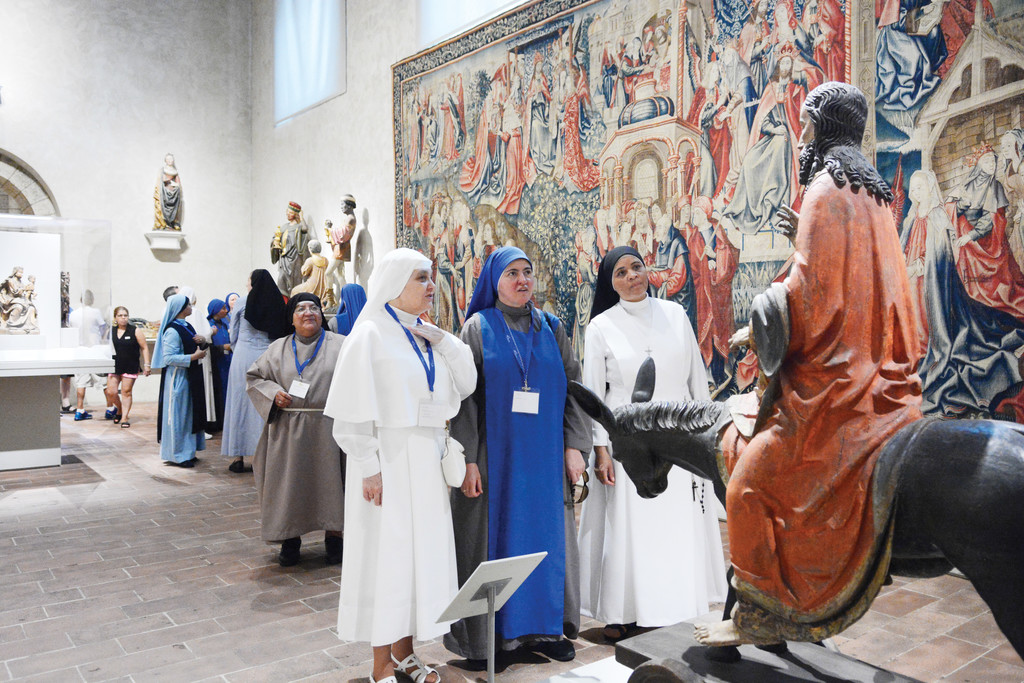 "Three sisters admire the 15th-century German ""Palmesel"" statue of Jesus on a donkey re-enacting Christ's entry into Jerusalem during their visit to The Cloisters in Manhattan July 22."
