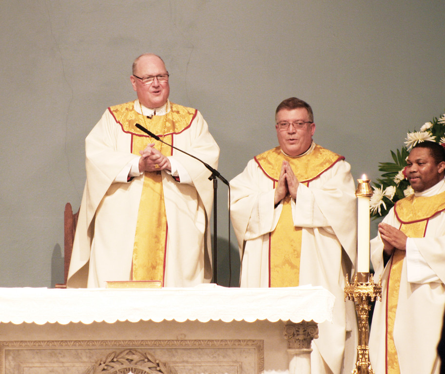 Cardinal Dolan is joined at the altar by Father Matthew Furey, pastor of Sacred Heart, and Father Innocent Nwachukwu, the parish's parochial vicar.