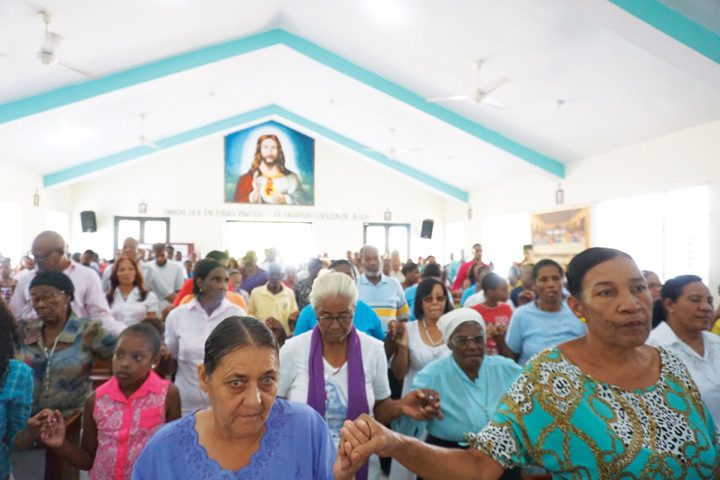 ON MISSION—Above, parishioners of Sagrado Corazon de Jesús (Sacred Heart of Jesus) in El Limon, Dominican Republic, hold hands for the Our Father at Mass.