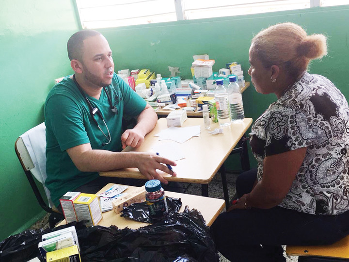 A doctor speaks with a patient in the free medical clinic set up by the missionaries from Our Lady of Angels parish in the Bronx.