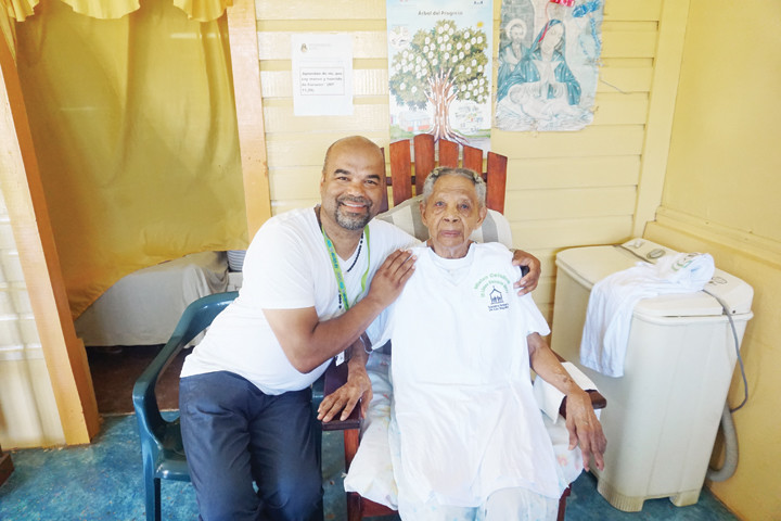 Eddy Correa, a mission organizer from OLA, visits a 96-year-old woman in her home.