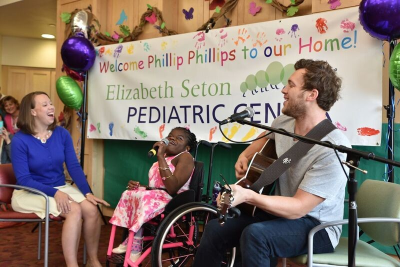 "Recording star and American Idol winner Phillip Phillips visited the Elizabeth Seton Pediatric Center in Yonkers Aug. 10 and brought along his guitar to strum a few of his songs for residents and staff. Above, Phillips gets a big assist on his hit ""Home"" from resident Stephanie Gabaud and her music therapist Kristen O'Grady."