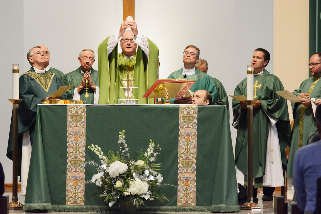 Cardinal Dolan elevates the Eucharist during Mass Sept. 9 to celebrate the parish's 25th anniversary.