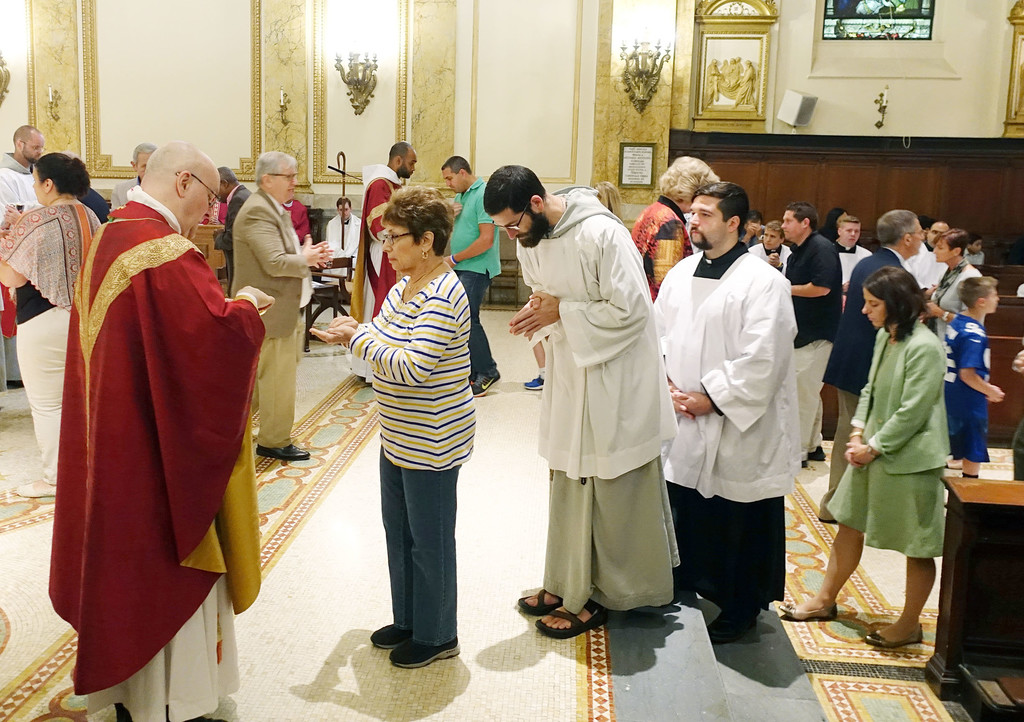 Brooklyn Auxiliary Bishop James Massa distributes Communion during the Mass of the Holy Spirit Sept. 10 marking the start of the academic year at St. Joseph's Seminary in Dunwoodie. Others enrolled in master's degree programs at the seminary, including clergy, religious and lay people as well as men in formation for the permanent diaconate, joined in the day, which included a picnic.
