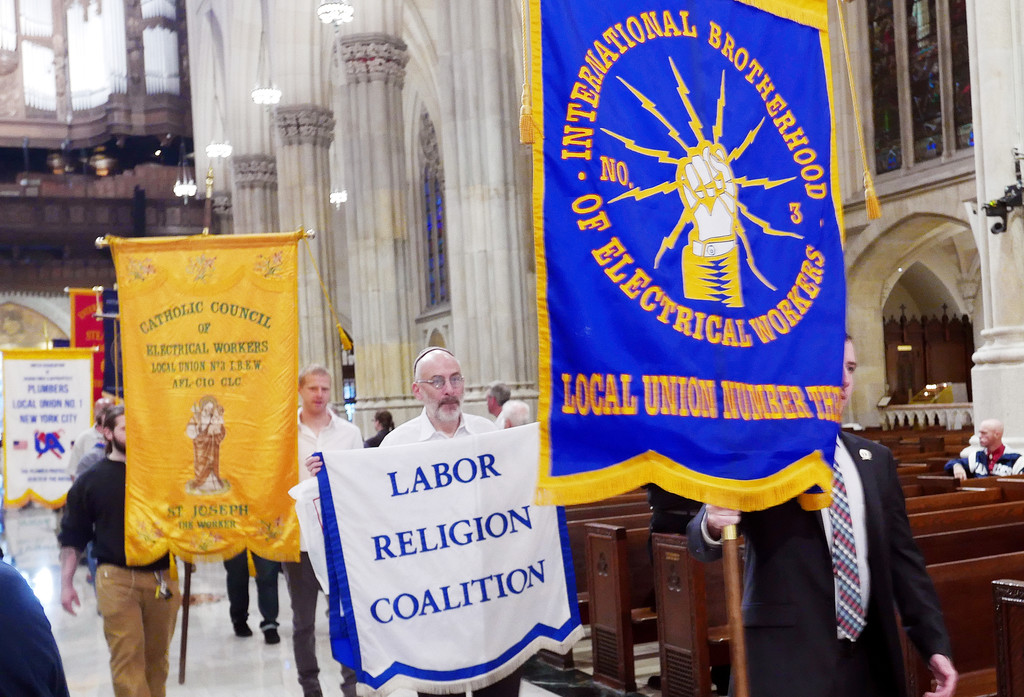Laborers, bearing banners, process into St. Patrick's Cathedral Sept. 9 for the annual Labor Mass.