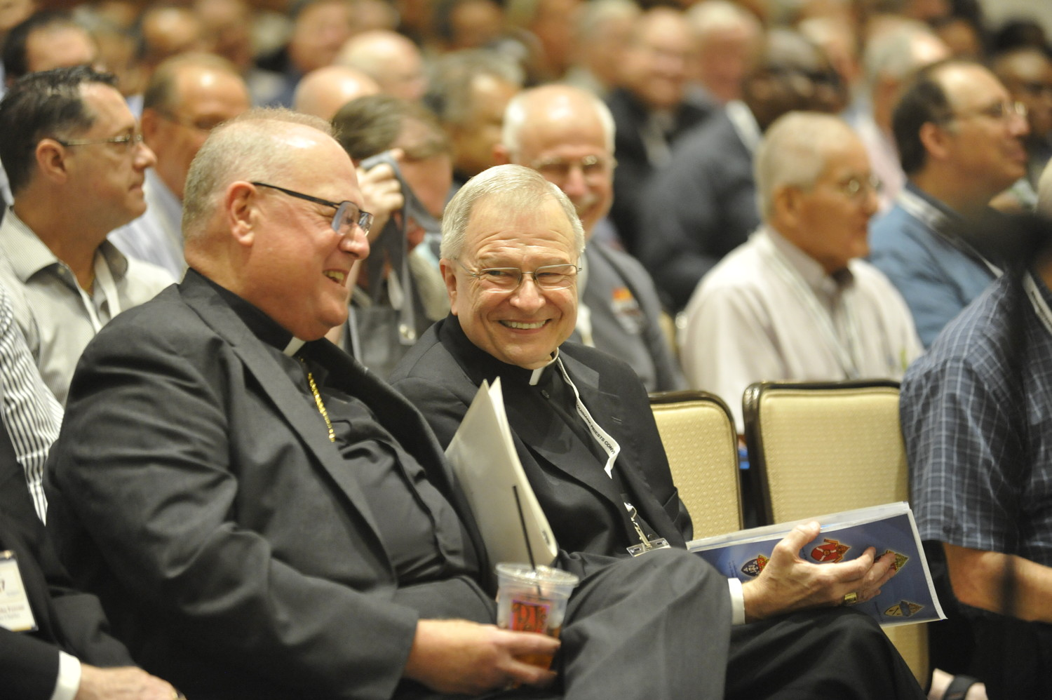 Cardinal Dolan and Archbishop Gregory Aymond of New Orleans share a laugh before the cardinal addressed the Louisiana Priests' Convention Sept. 19.