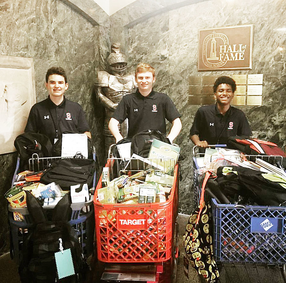 CHEERFUL GIVERS—Archbishop Stepinac High School students, from left, freshman Devlin Hose, senior John Skelton and sophomore Tyler Stewart show some of the many school supplies Stepinac collected to help a high school in Texas affected by Hurricane Harvey.