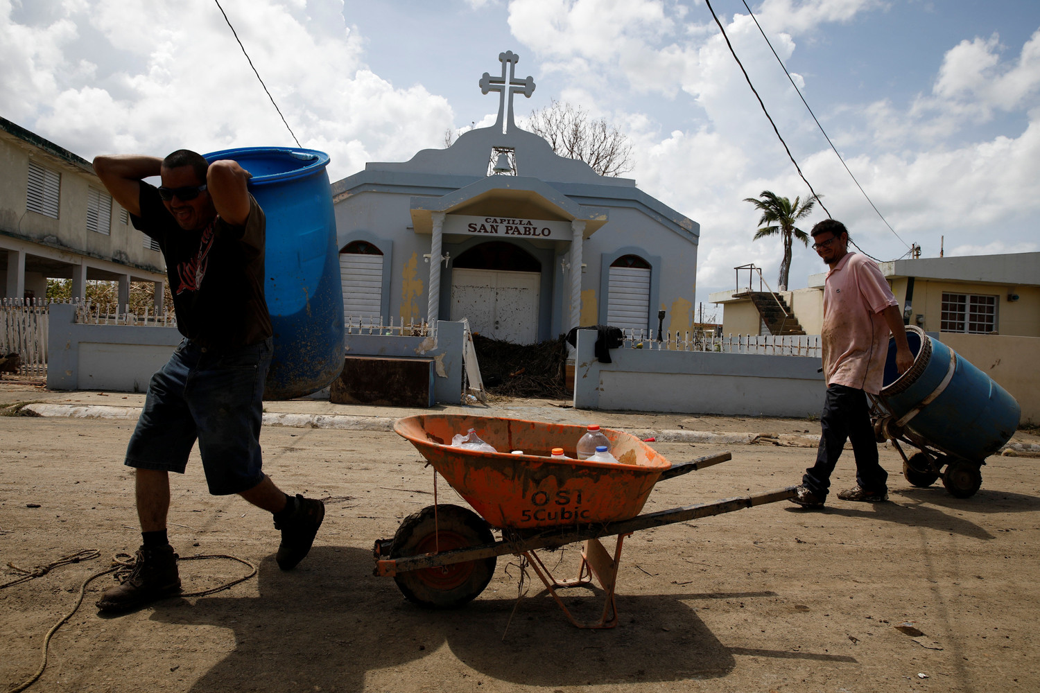 BASIC NEEDS—Men carry a container filled with water past a damaged church Sept. 24 after the area was hit by Hurricane Maria in Toa Baja, Puerto Rico.