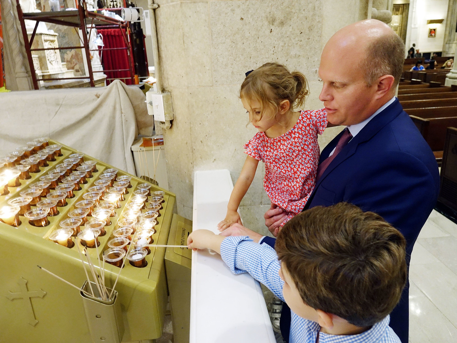 A curious Lillie Seton Lamb, 3, a descendent of Mother Seton, watches as her brother George lights a candle at the altar under the guidance of their father, Seamus Lamb.