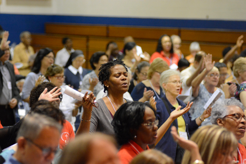 JUBILATION—Participants at a conference of the Catholic Charismatic Renewal movement Oct. 7 at Cathedral High School in Manhattan sing songs of praise.