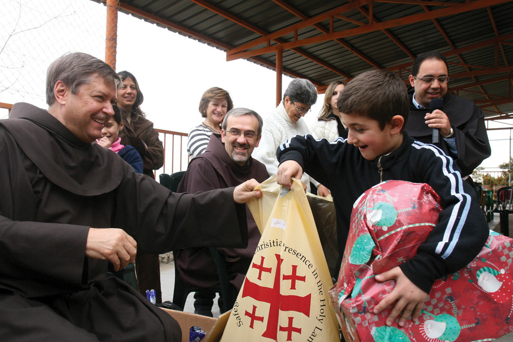 CHRISTMAS JOY—Father Peter Vasko, O.F.M., president of the Franciscan Foundation for the Holy Land, helps to distribute Christmas gifts at the foundation's Bethlehem Boys Home.