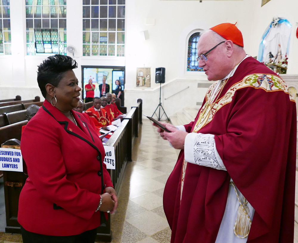 The cardinal receives an image of St. Thomas More from Bronx District Attorney Darcel Clark.