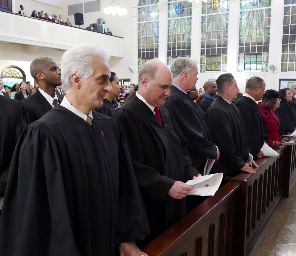Judges in the front pew participate in the Mass.