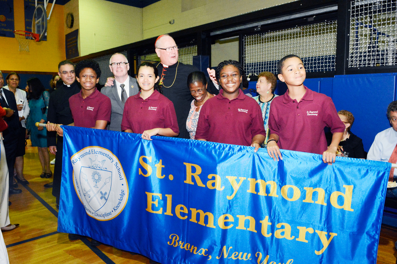 Cardinal Dolan stands behind students of St. Raymond's Elementary School at a reception following Mass in the Bronx Sept. 16. St. Raymond's Elementary School, with 900 students, is one of three parish schools with St. Raymond's High School for Boys and St. Raymond's Academy for Girls.