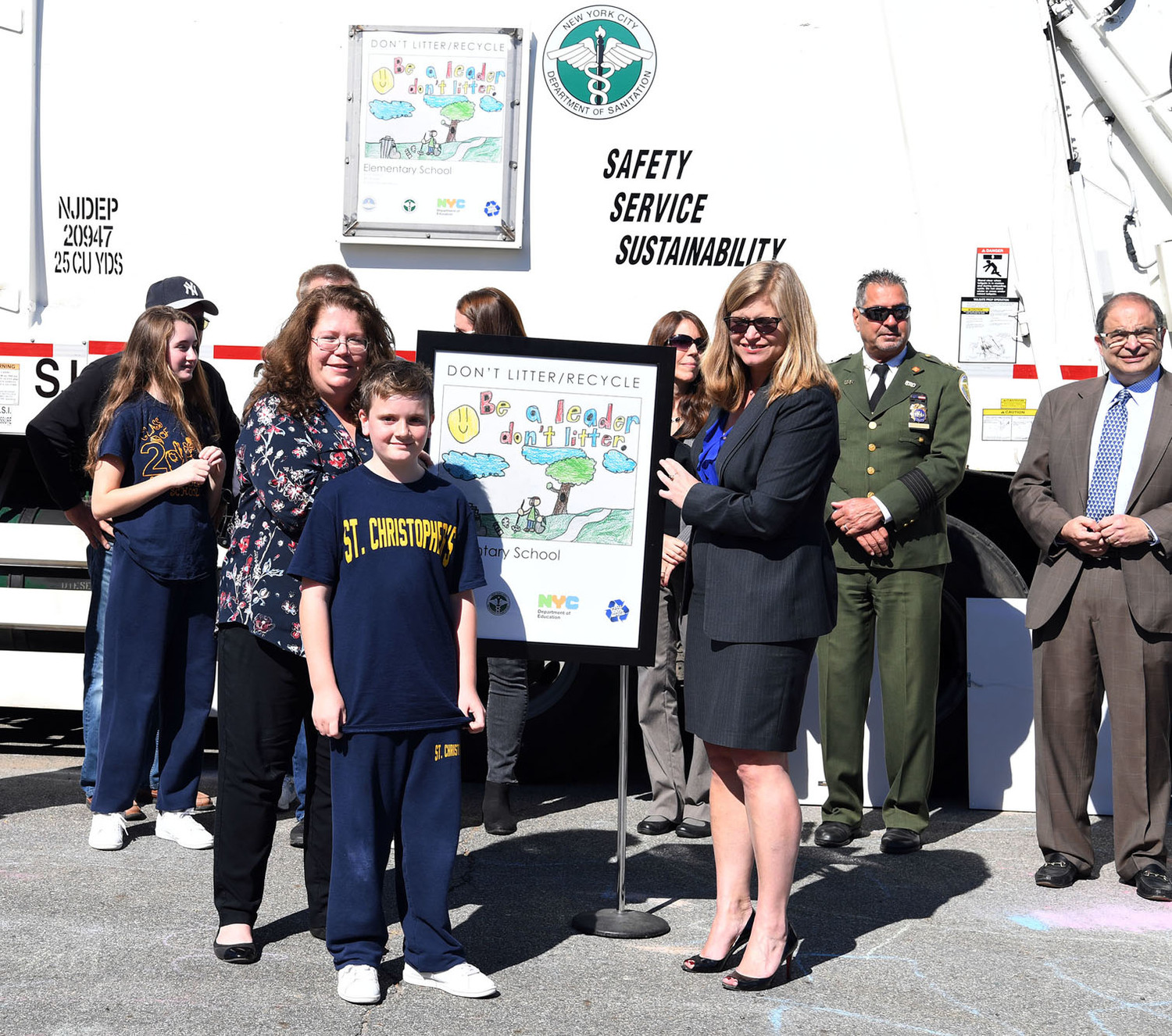 Ryan Schnur of St. Christopher's School on Staten Island is shown alongside his winning artwork held by his principal, Catherine Falabella, and DSNY Commissioner Kathryn Garcia. The work is showcased on a borough sanitation truck, behind them.