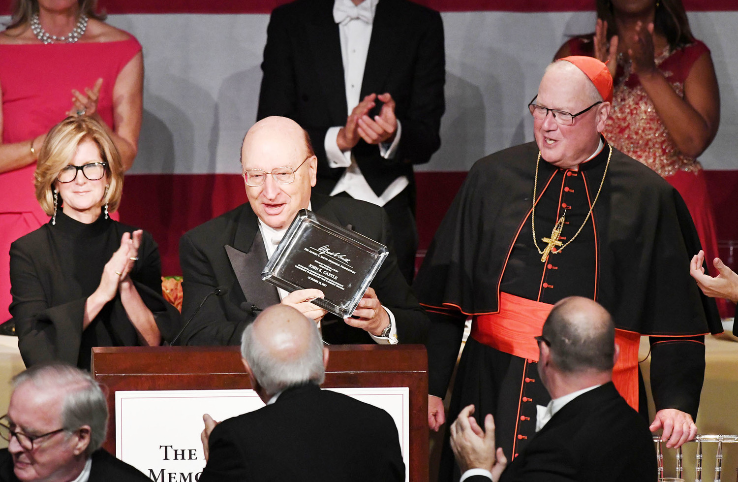 "Mary Callahan Erdoes, vice chair of the Alfred E. Smith Memorial Foundation, applauds as John K. Castle accepts ""The Happy Warrior"" award as Cardinal Dolan looks on."