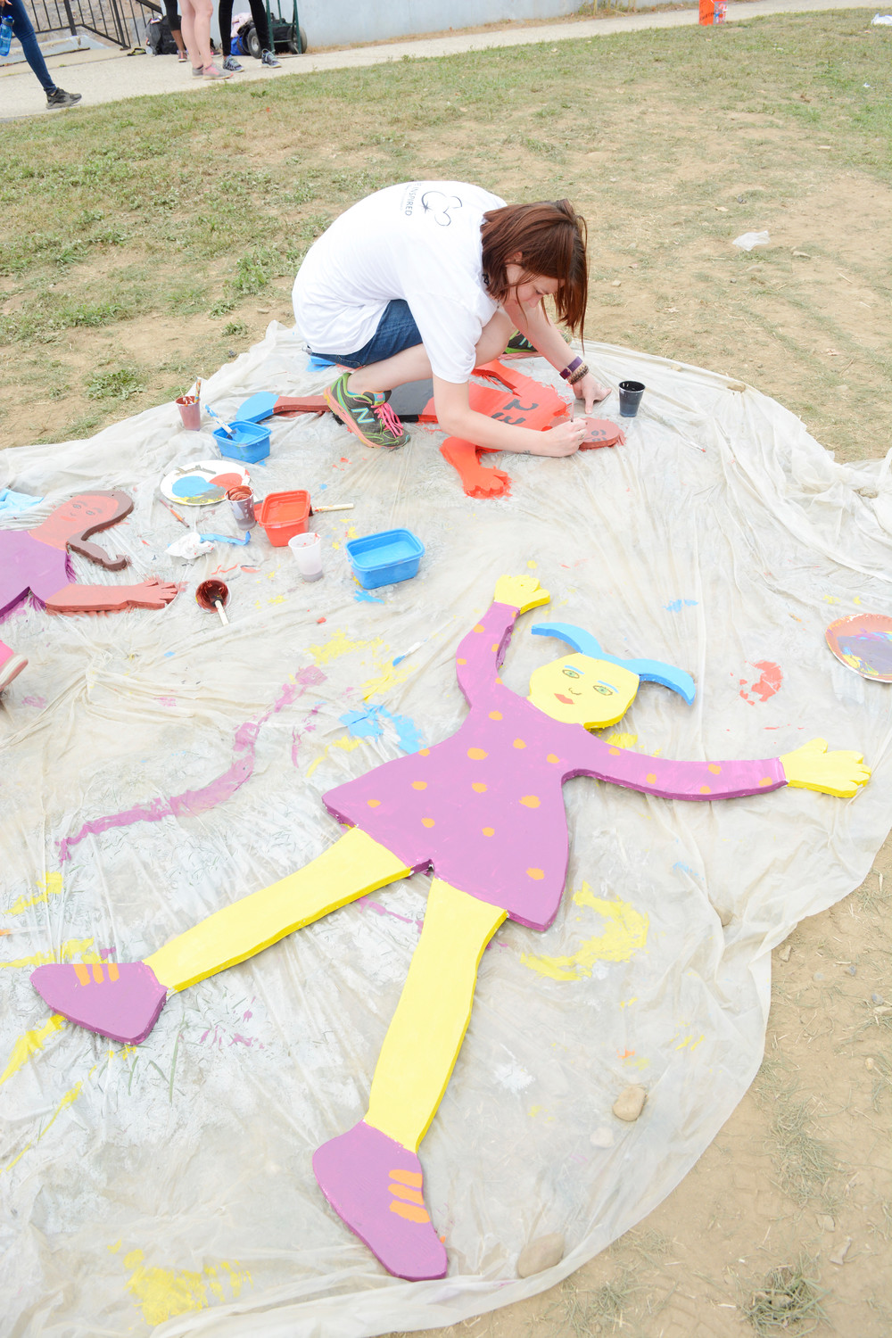 A volunteer paints large cutouts and other decorative items for the new playground at the Lawrence Hickey Center for Child Development in the Bronx Oct. 5.