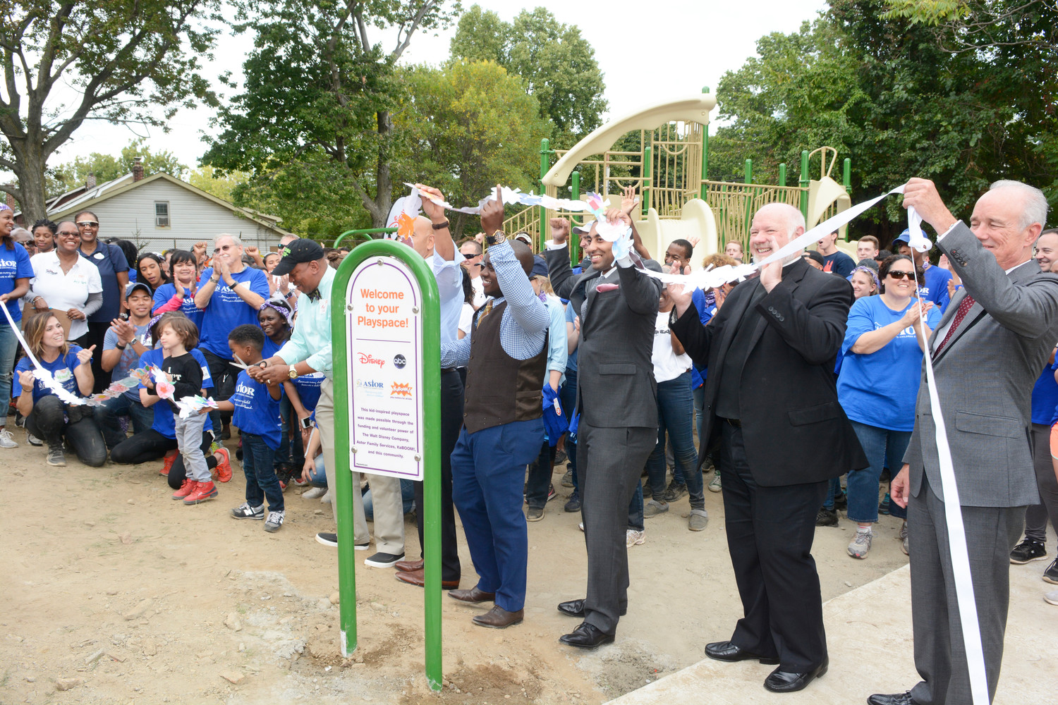 Msgr. Kevin Sullivan, executive director of Catholic Charities in the archdiocese, second from right, participates in the ribbon-cutting ceremony to open the playground.