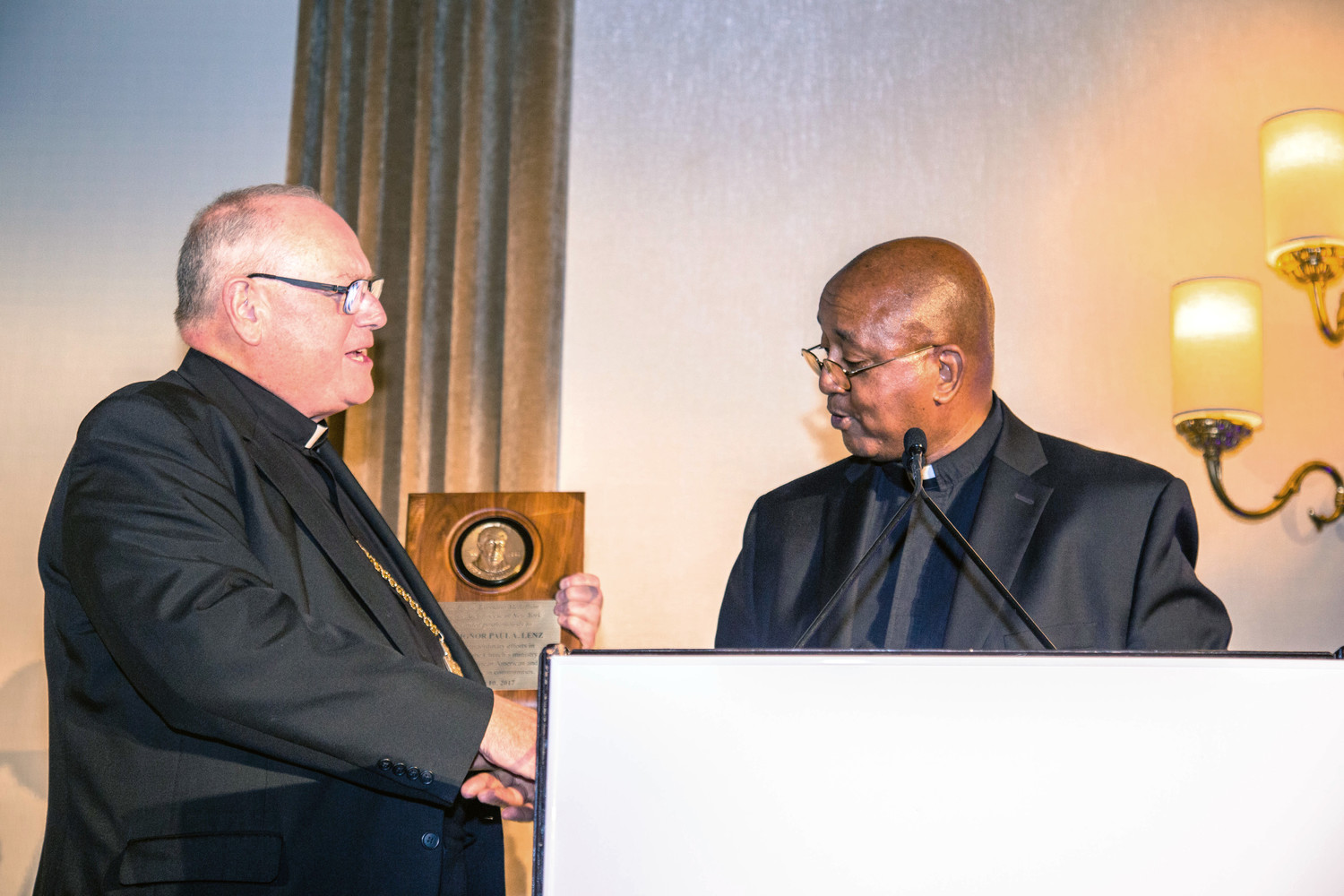 Cardinal Dolan, left, accepts the award given posthumously to Msgr. Paul A. Lenz, a former national director of the Black and Indian Mission Office, from Brother Tyrone Davis, C.F.C., executive director of the archdiocesan Office of Black Ministry.
