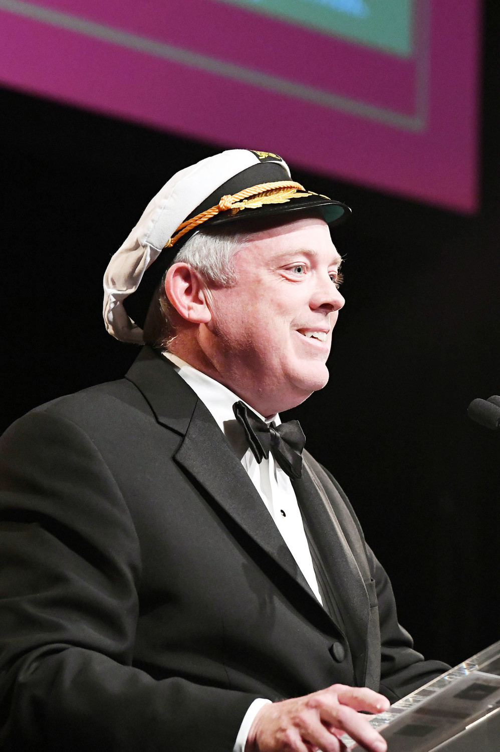 LaRue gets into the spirit of the occasion by wearing a nautical cap as he conducts a fund-raiser for a cruise.