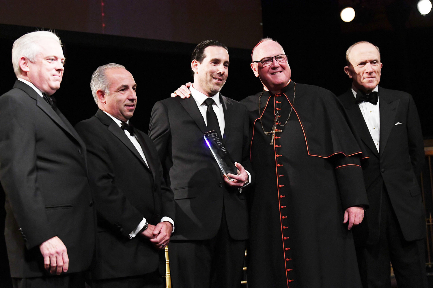 Michael Segal, CEO of PharmScript, center, receives the ArchCare Partnership Award at the ArchCare Gala at Gotham Hall in Manhattan Nov. 1. Standing, from left, are Scott LaRue, president and CEO of ArchCare, Michael Rosenblum, vice president of client management for PharmScript; Segal; Cardinal Dolan; and Francis J. Serbaroli, chairman of ArchCare's board of trustees.