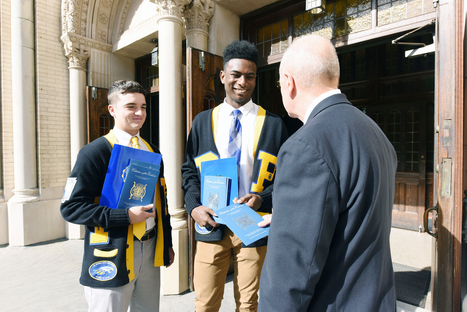 From left, St. Peter's Boys High School seniors Peter Rotondo and Jordan Fox distribute programs before the school's Centennial Mass at St. Peter's Church on Staten Island Oct. 22.