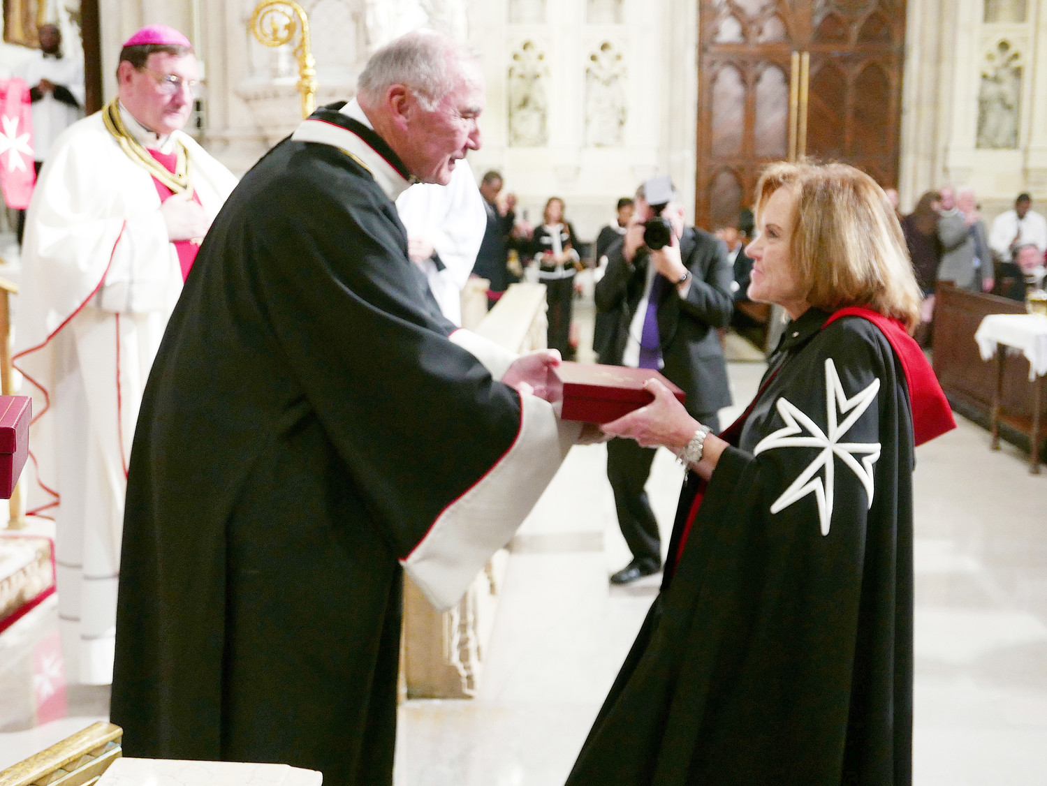 Wearing the traditional black Order of Malta robes, the new knights and dames are presented their crosses, encased in boxes, from Jack Pohrer, president of the American Association of the Order of Malta, above. They were accepted into the order during a Nov. 3 Mass at St. Patrick's Cathedral celebrated by Bishop Jean Clément Laffitte, prelate of the Order of Malta, pictured behind Pohrer at top right