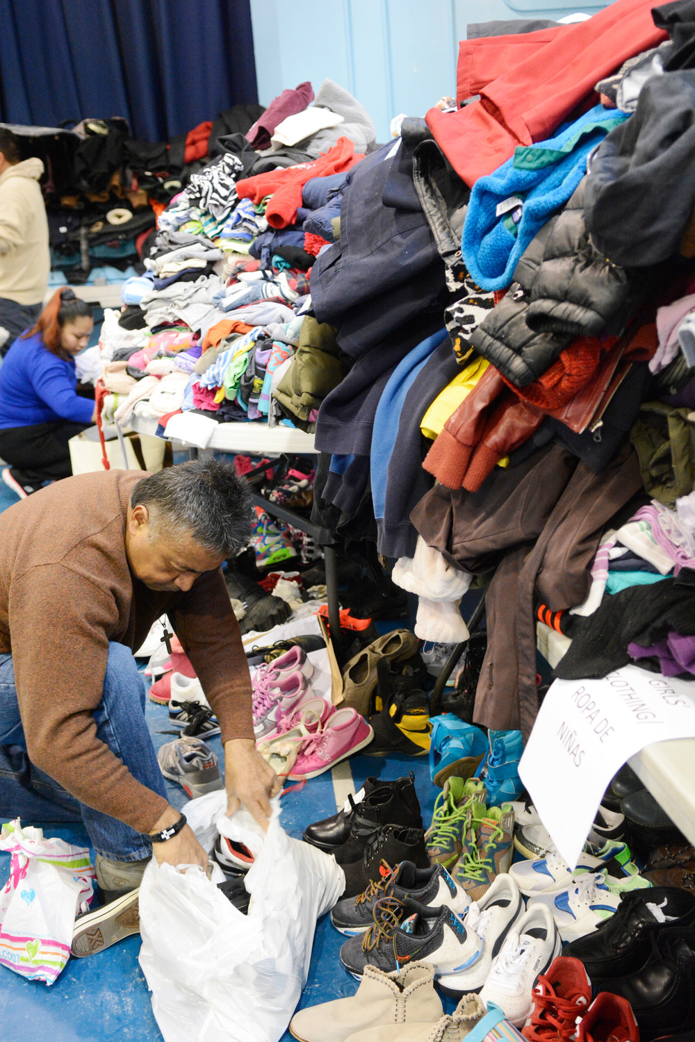 Santiago Gutierrez and Lorena Velasquez of St. Martin of Tours parish in the Bronx sort clothes on the gymnasium floor at the former St. Martin of Tours School during a community-wide clothing and food drive Dec. 30 to aid victims of an apartment fire that broke out two days earlier and claimed 12 lives.