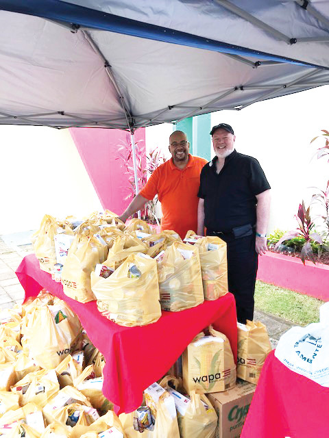 SERVICE WITH A SMILE—Msgr. Kevin Sullivan, executive director of archdiocesan Catholic Charities, and Eddie Silverio, a New York Catholic Charities employee, prepare to give away food packages at the John Cardinal O'Connor New York Foundling Head Start center in Coamo, Puerto Rico, last month.