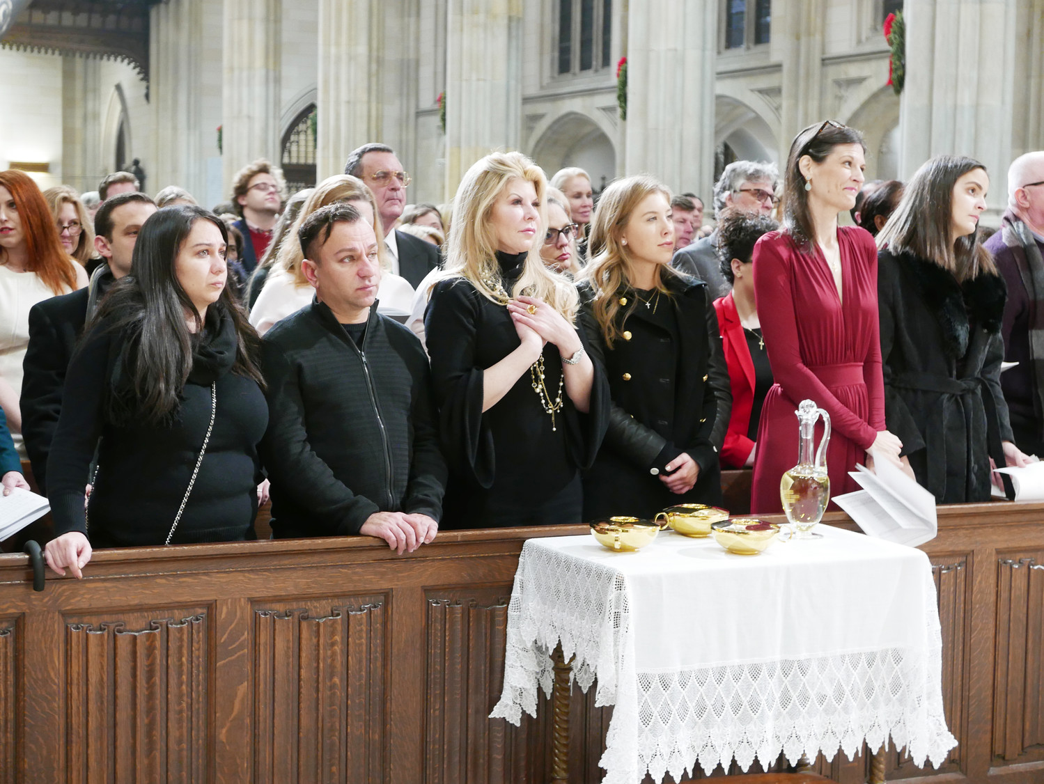 Members of the congregation listen prayerfully to words from the altar. In front of the congregation, the offertory gifts are carefully arranged on a table.