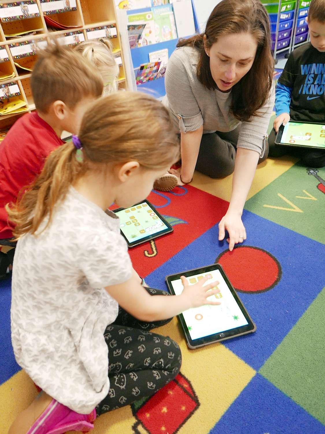 Pre-K student Victoria Fertucci learns the basics of using an iPad from teacher Christy Marks.
