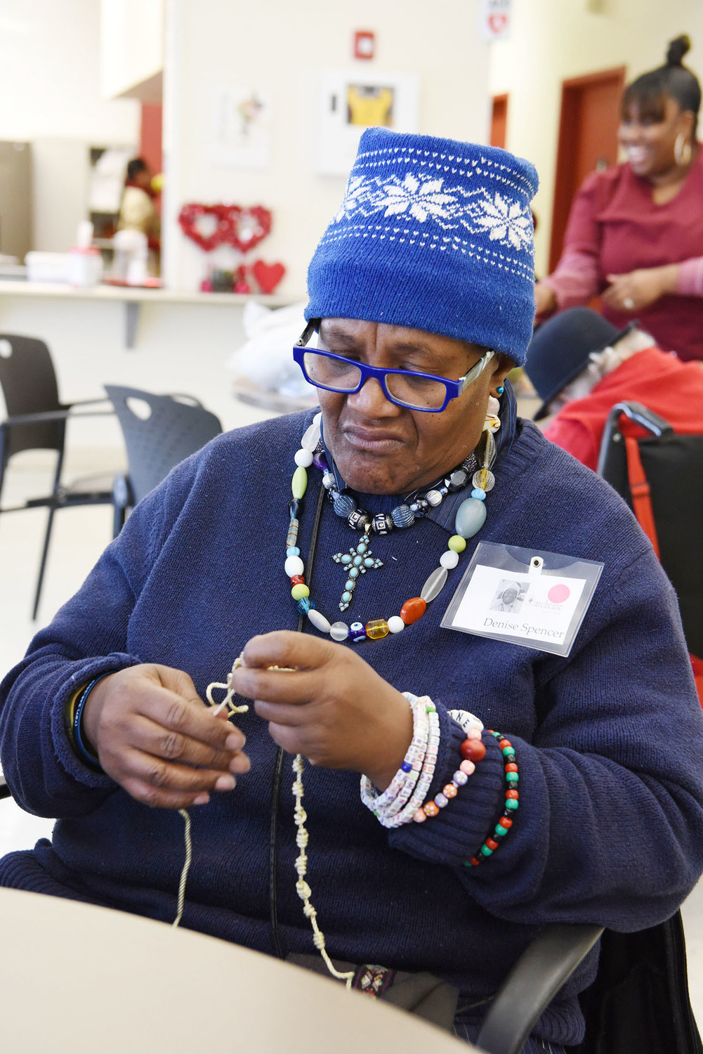 Day center participants at ArchCare on Staten Island have finished the last of 50 hand-knotted rosaries for U.S. troops. Denise Spencer works on one of the rosaries.