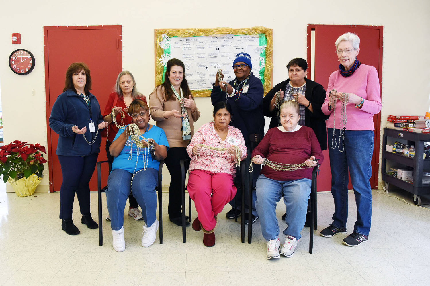 A group photo shows some of the participants in the rosary-making project. From left, seated, are Marcia Harris, Analisa Mascarinas and Mary Casey. Standing, from left: Cynthia Cobb, ArchCare transportation coordinator; Ana Blanco, Lauren Abate, ArchCare alternate care site coordinator; Denise Spencer, Mildred Lebron, and Neale Steiniger, 