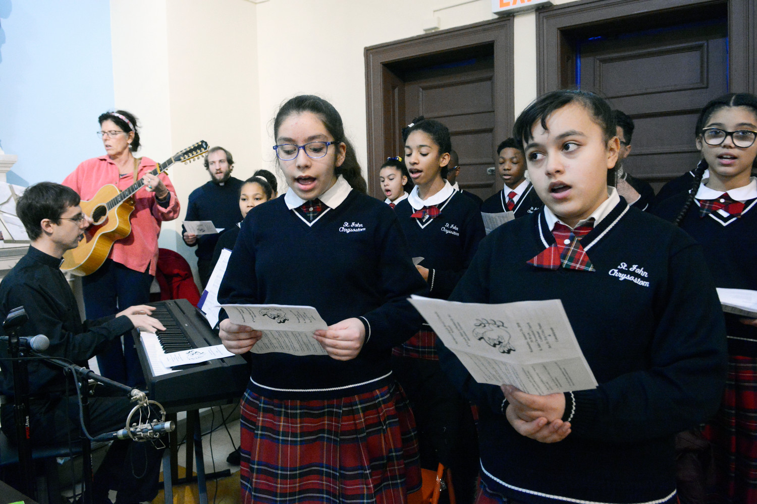 sixth-grader Lexyne Rivera, left, and seventh-grader Melania Rodriguez sing with the St. John Chrysostom School choir at Mass.