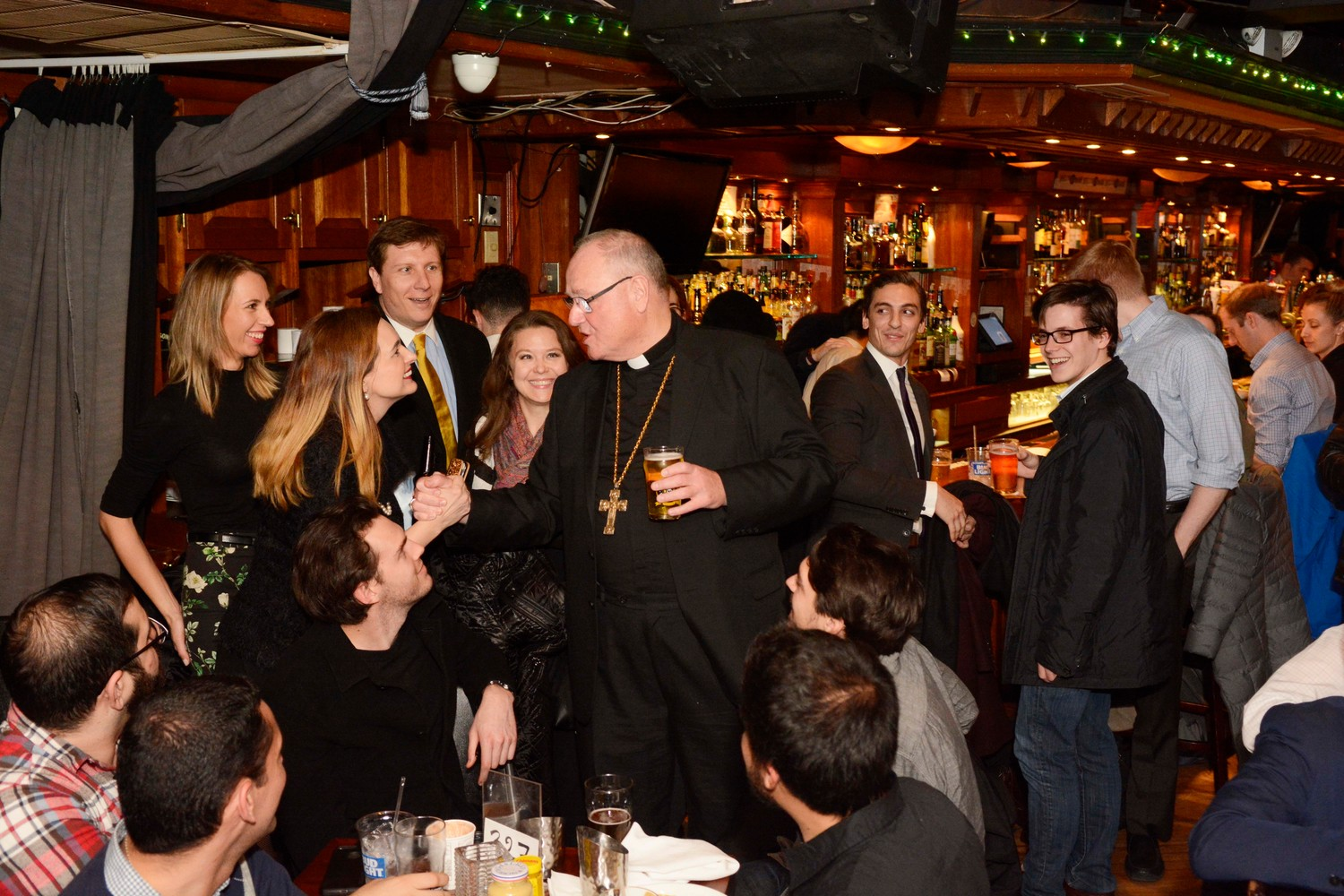 "The cardinal chats with young adults during ""Theology on Tap with Cardinal Dolan"" at Connolly's Pub and Restaurant in Manhattan Feb. 12. The archdiocese's Office of Young Adult Outreach sponsored the event."