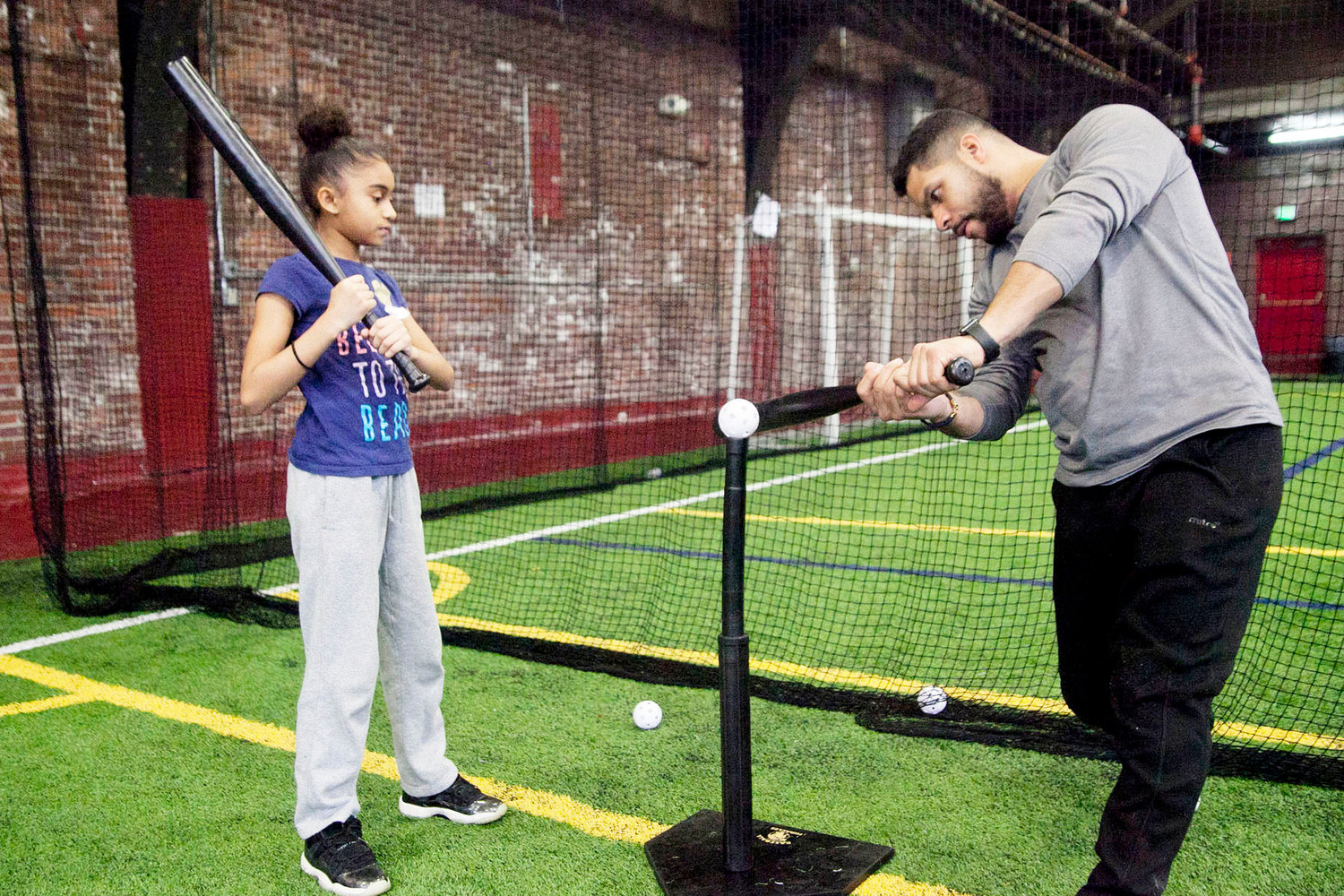 Steve Marrero, a coach with Newburgh Baseball Instruction, gives Jaslene Cheatham hitting tips.